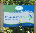 A sign outside a building on a grassy lawn: Community Living Belleville and Area.