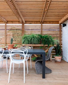 An outdoor living space with a dining area and pergola.