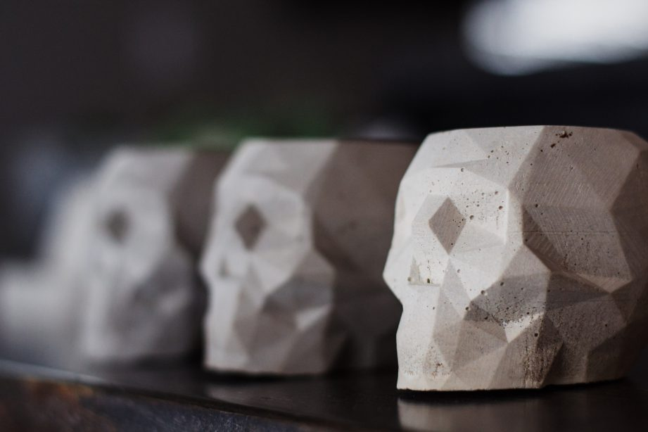 A row of concrete skull plant pots on a table.