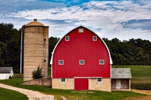 A tall silo next to a red barn.