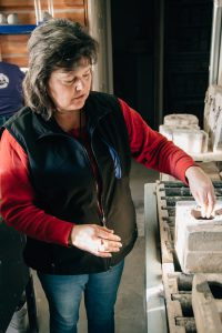 Marleen Murphy in her Millside Ceramics studio, explaining the process of filling the moulds.