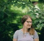 Shelby Lisk standing under a green canopy of leaves and branches.