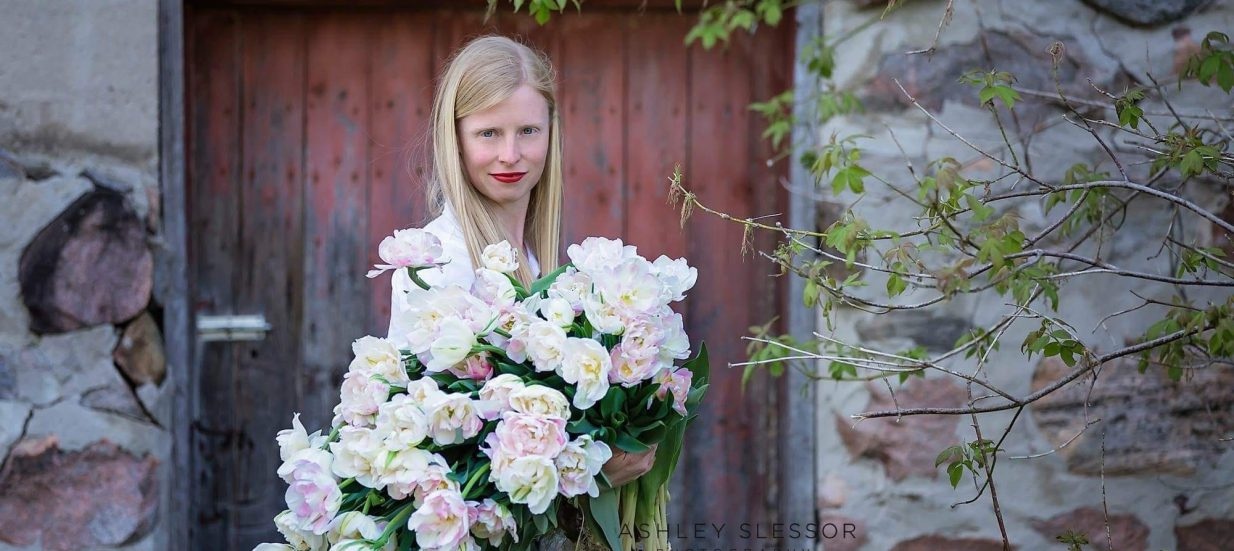 Melanie Harrington holding a bouquet of flowers in front of a barn door.