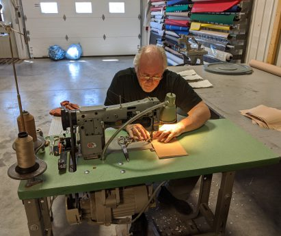 A man sitting behind a table sewing.