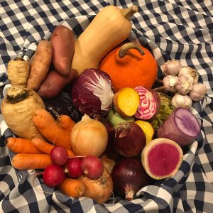 A pile of mixed produce on a black-and-white checkered blanket.