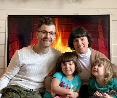 A family of four sits in front of a fireplace.