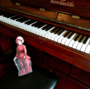 A cardboard cutout of a doll on a piano bench.