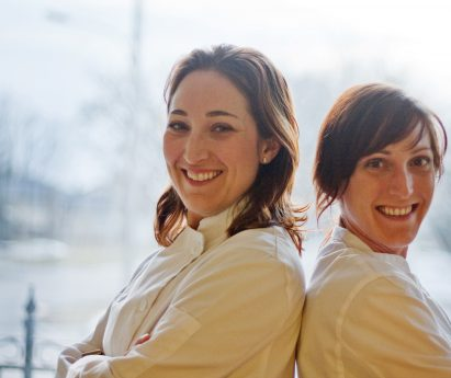 Two women in chef coats standing back to back.