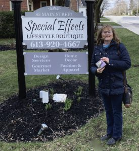 A woman standing next to a sign that says, Special Effects Lifestyle Boutique