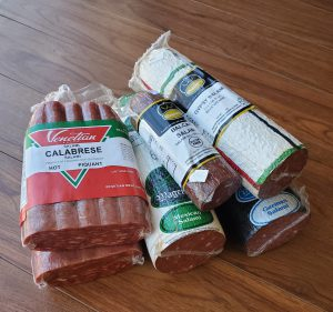 Packages of cured meats stacked on a wooden table.