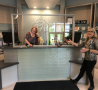 Two women standing at a reception desk with plexiglass.