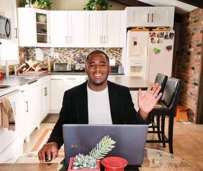 A man sitting at a kitchen table working at a laptop.