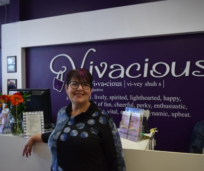 A woman standing in front of a purple sign with the word 'Vivacious' on it.