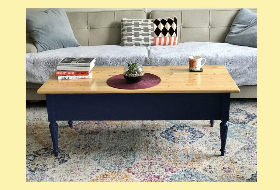 A coffee table on a rug in front of a grey couch.