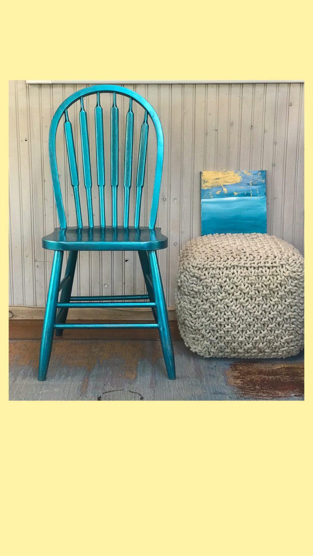 A blue chair next to a grey cushion.