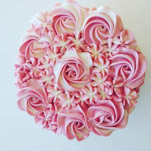 The top of a cake with swirly pink icing.