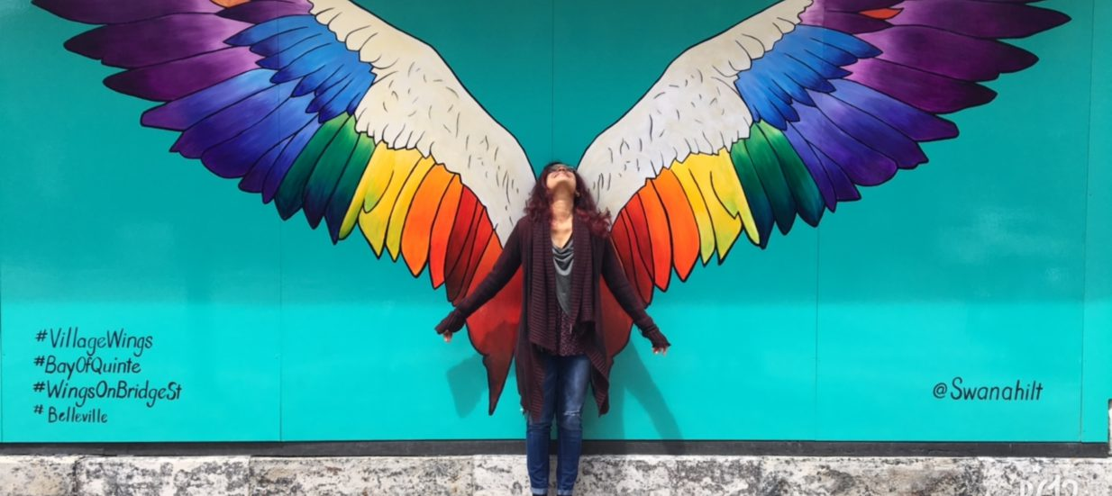 A person standing in front of a turquoise wall with wings painted on the mural.