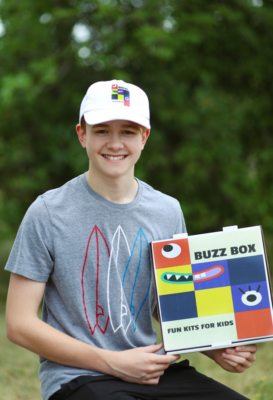 "A person standing holding a box that says, ""Buzz Box Fun Kits"""