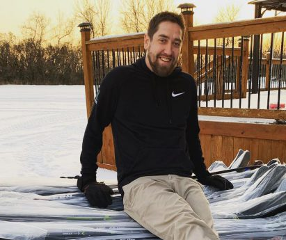 A person sitting on a pile of hockey sticks in the snow. Joey Walsh, owner of HockeyStickMan in Belleville, shares why the Bay of Quinte is a great fit for the business.