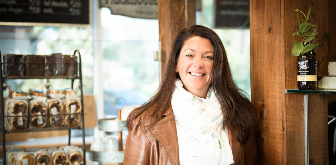 A person wearing a white shirt and brown jacket standing next to a wood beam. Melissa Strecker, owner of Farmer's Daughter Sub Shoppe in Quinte West, shares how the business has been Makin' It Work through COVID-19.