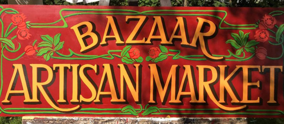 A hand-painted sign with text: Bazaar Artisan Market. Kaya Pereira, owner and curator of the Bazaar Artisan Market in downtown Belleville.