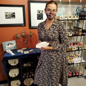 A person wearing a mask standing in front of a wall of art. Kaya Pereira, owner and curator of the Bazaar Artisan Market in downtown Belleville.