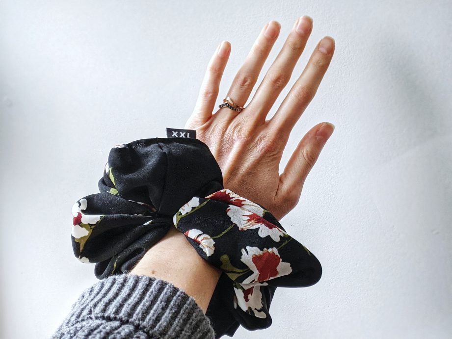 A person's arm extended wearing a black and floral scrunchie.