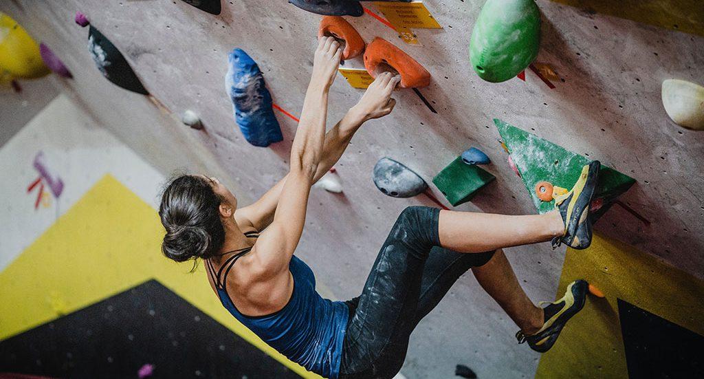 Female rock climbing indoors