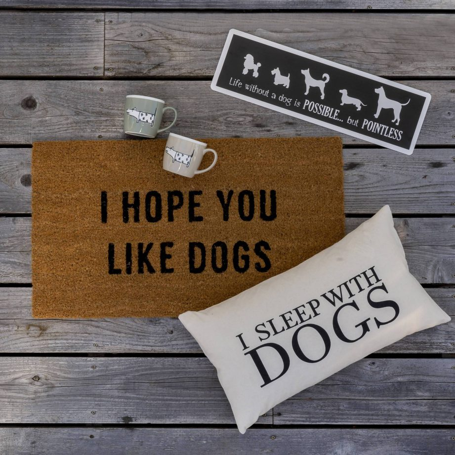 A door mat that says 'I hope you like dogs', a pillow that says 'I sleep with dogs' and two mugs on a wood background.