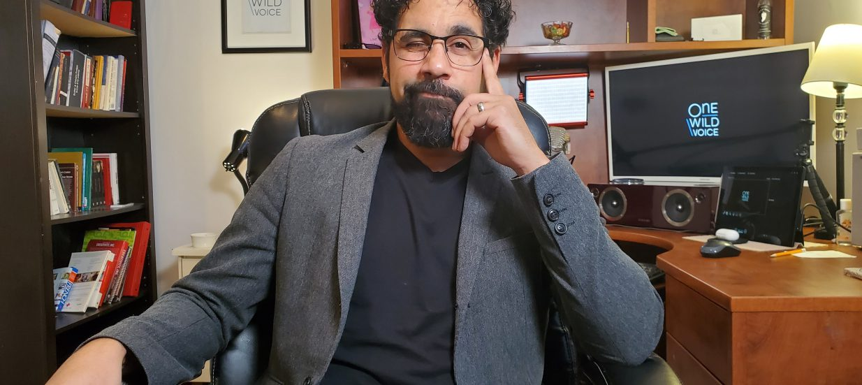 A person in a grey suit sitting in an office chair.