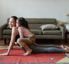 A person doing a yoga pose with a child on their back.