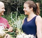 Two people standing facing each other holding bunches of garlic.