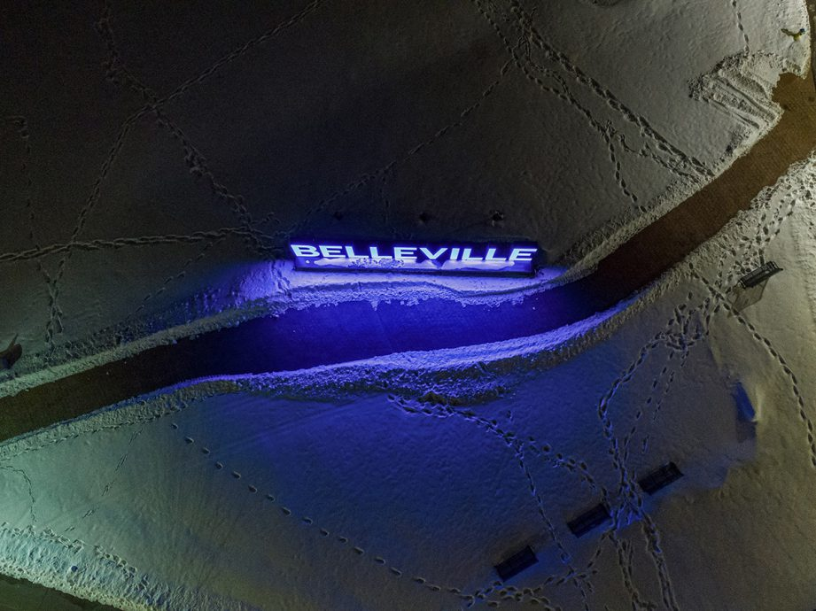 Aerial shot of snowy ground with footprint and a glowing 'Belleville' sign.