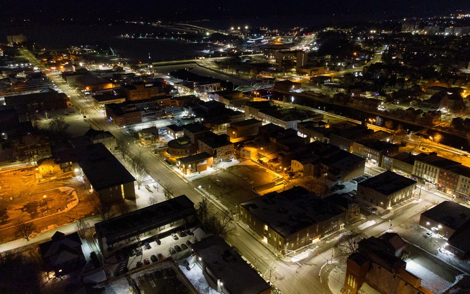 Aerial shot of a city at night with lots of lights on.