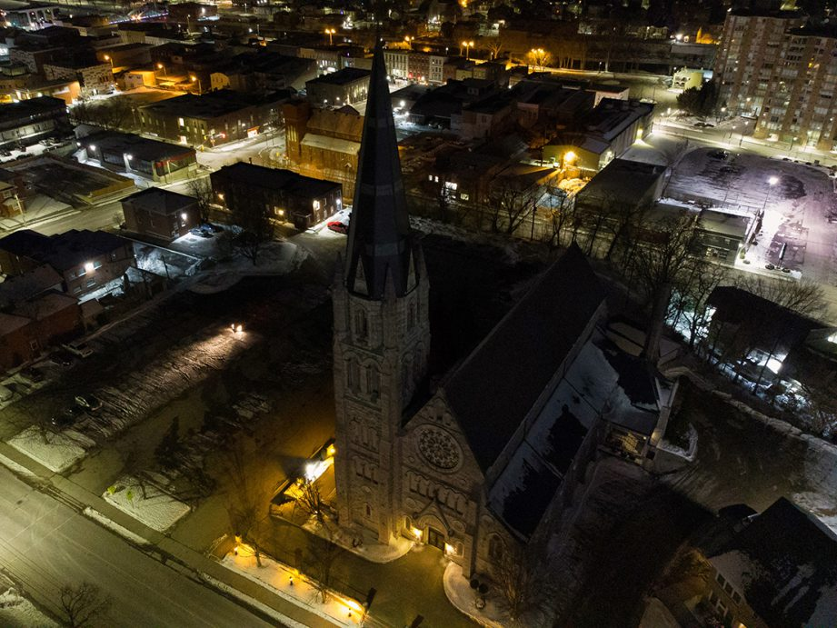 An aerial photo of a church at night with lights and buildings in the background.
