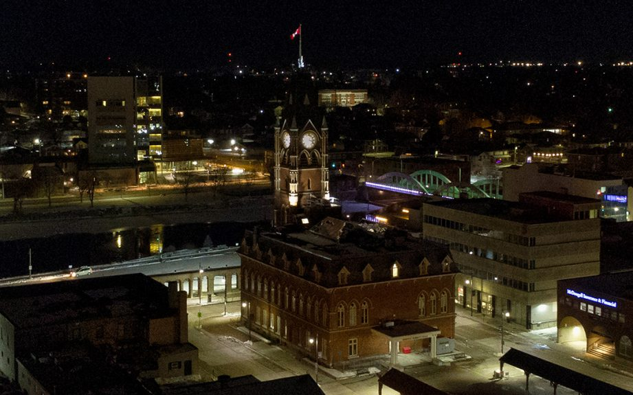 An aerial photo of a tall redbrick building, Belleville City hall, at night.