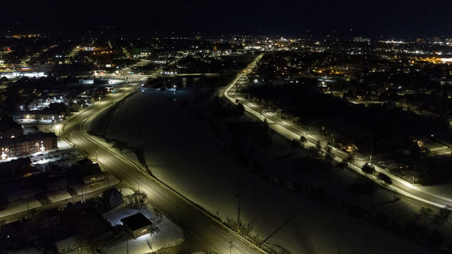 Aerial shot of a river at night with city street lights alongside it.