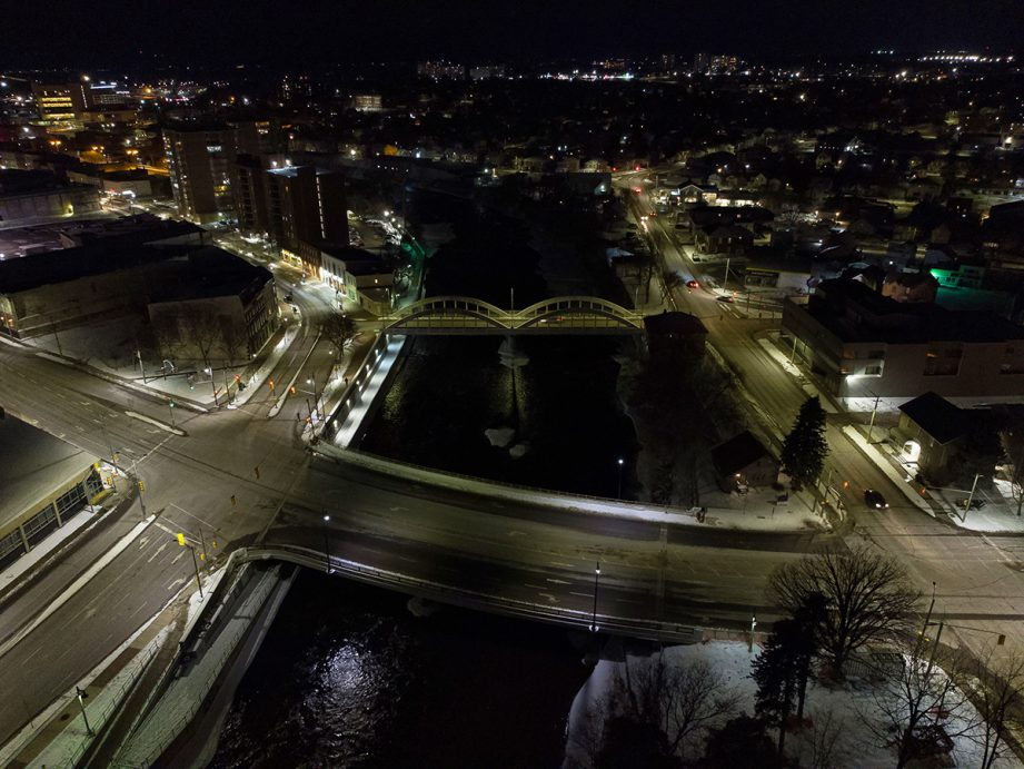 Aerial shot of a river at night with two bridges and city street lights alongside it.