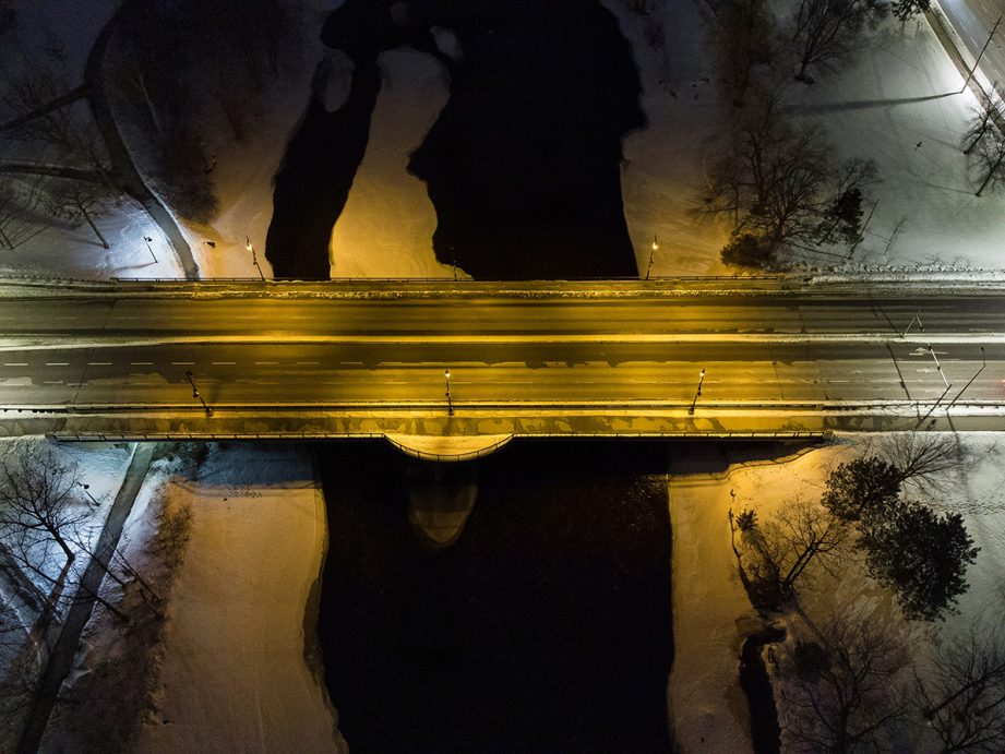 Aerial photo at night of a road crossing over a river.