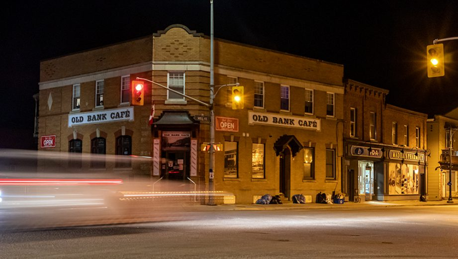 A street intersection at night with blurred cars. A building with a sign: Old Bank Cafe.