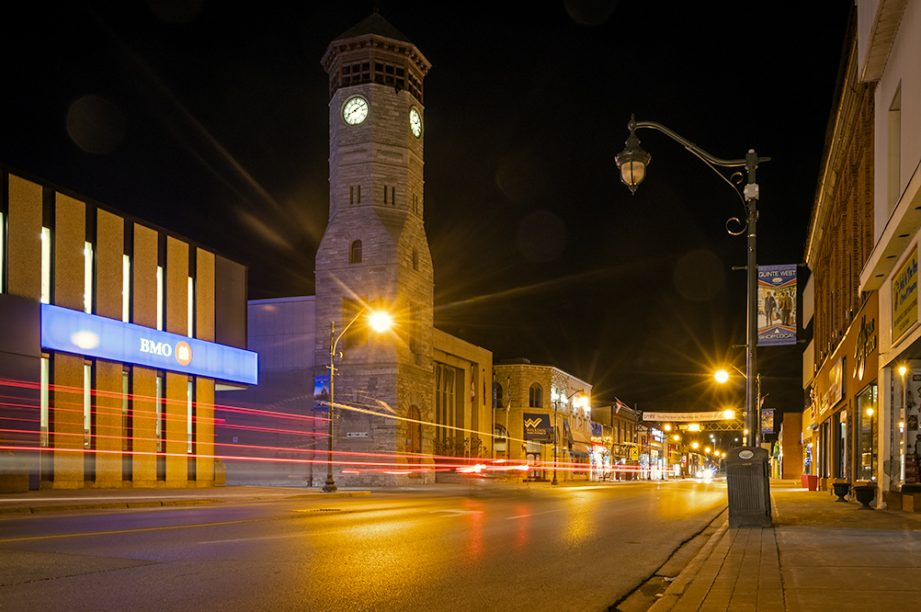 A streetscape at night with a large clocktower and light streaks from cars.