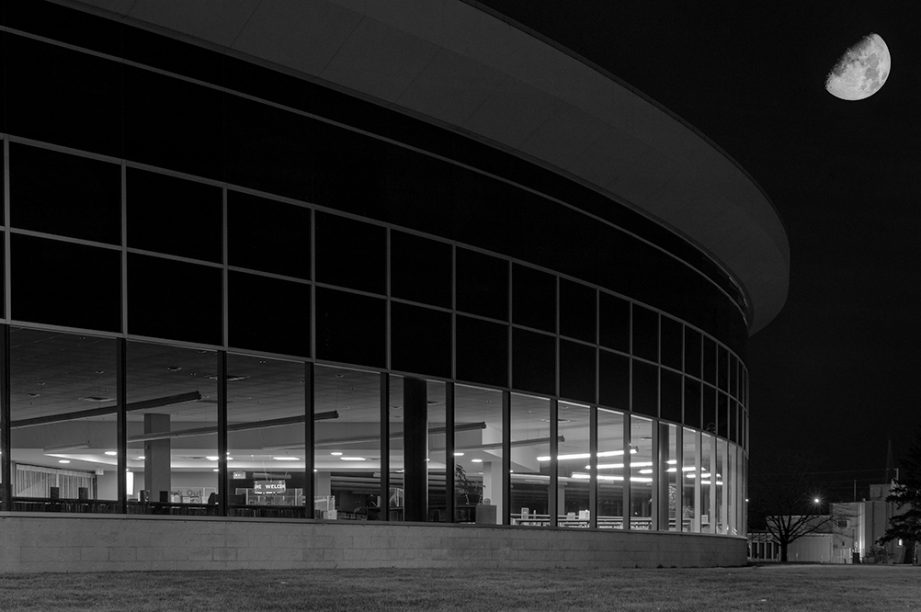 A black and white photo of a curved building with many windows, and the moon high in the sky.