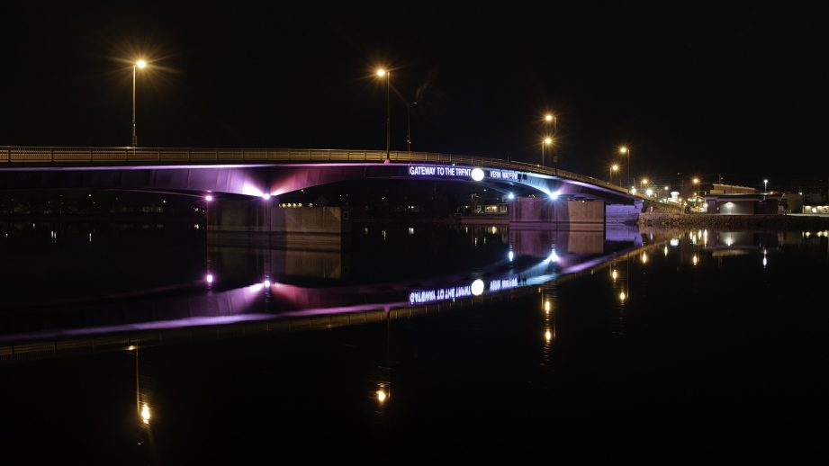 A bridge at night with lights reflected in the water below.