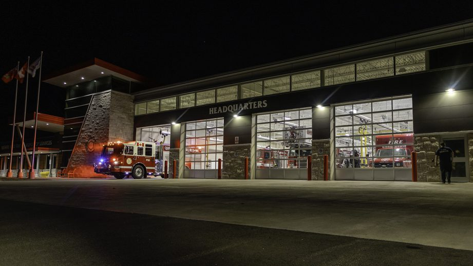 A fire department at night with lights on.