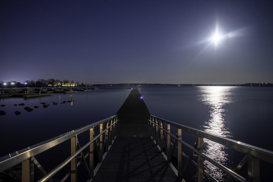 A boardwalk along the water at night with a bright moon in the sky.