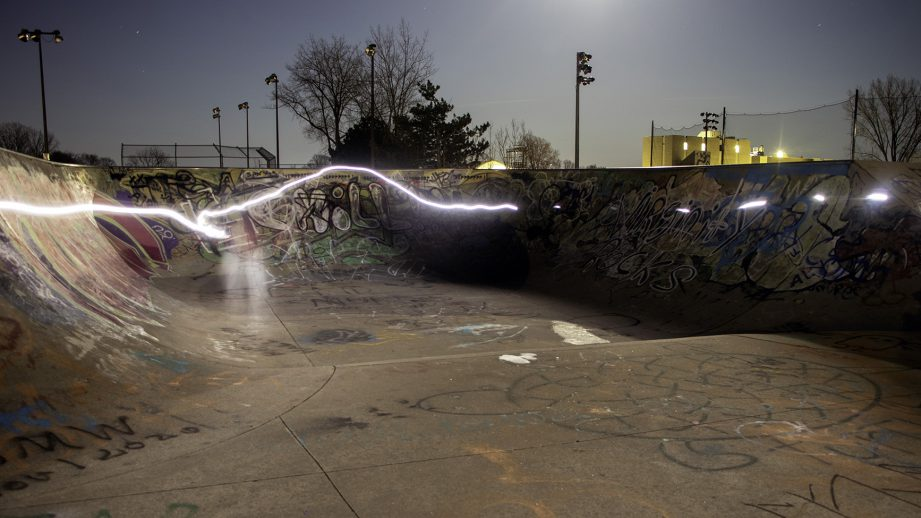 A skate park at night with a light streak around the edge.