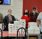Seven masked people standing behind a table piled with takeout boxes.