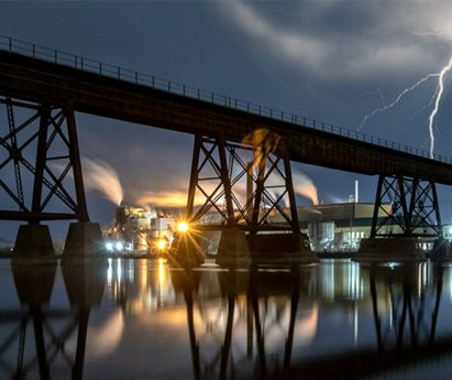 A lightning bolt at night behind a tall bridge crossing a river.