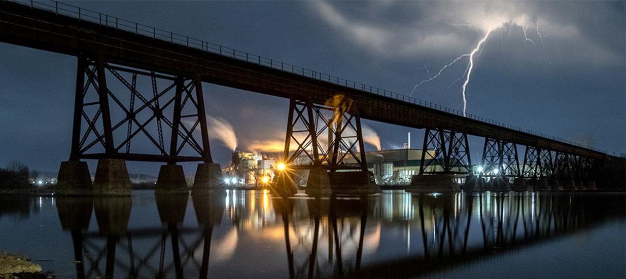A lightning bolt at night behind a tall bridge crossing a river.