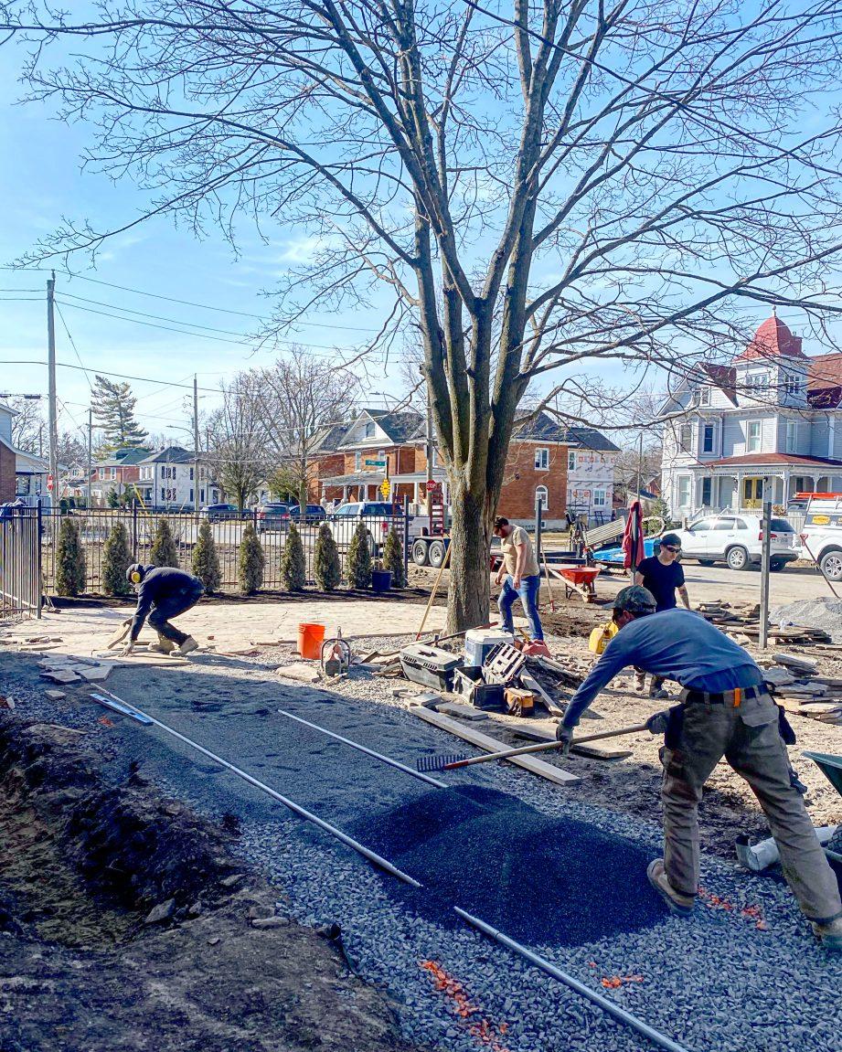 People doing yardwork and raking gravel.